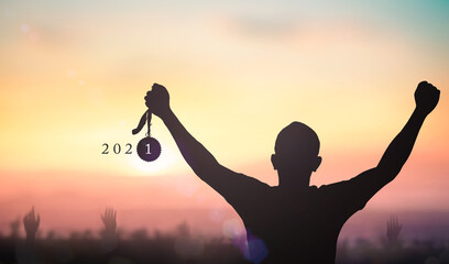 Success new year 2021 concept: Silhouette winner hand holding gold medal reward with text for 2021 against blurred sunset background