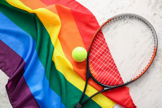 Rainbow LGBT flag and tennis racket with ball on light background