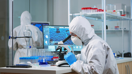 Chemist researcher in overall looking at bacteria sample from glass equipment in modern equipped laboratory. Examining vaccine evolution using high tech for researching treatment against covid19 virus - fototapety na wymiar