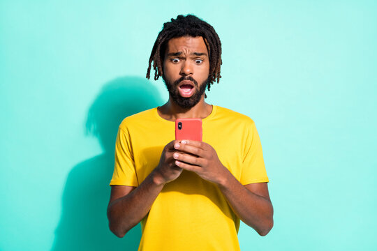 Photo portrait of scared unhappy afro american guy holding phone in two hands isolated on vivid teal colored background