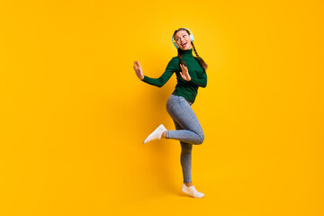 Full length body size photo funny woman listening blue earphones dancing looking blank space isolated on bright yellow color background