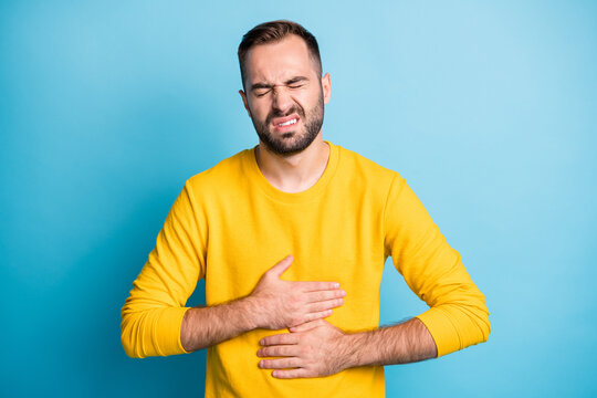 Photo portrait of man grimacing touching stomach injury poisoning disbalance diarrhea isolated on bright blue color background