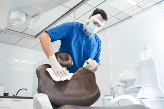Serious doctor wipes the dentist chair and preparing office
