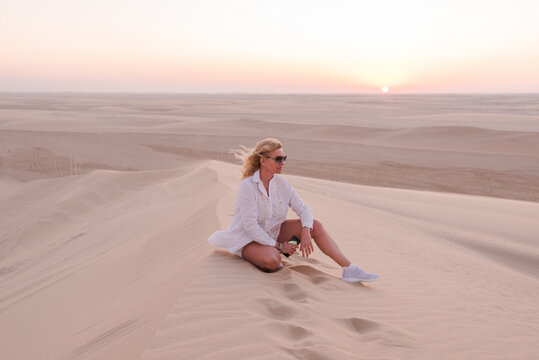 Woman on a hill in the desert at sunset, Qatar