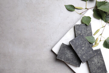 Wall Mural - Natural tar soap bars and birch branches on light grey stone table, flat lay. Space for text