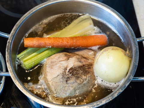 boiling of beef stock with vegetables on stove at home kitchen