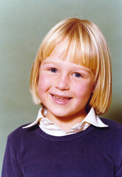 Vintage 1978 yearbook school image of a smiling young girl with blond hair and blue eyes with blue sweater and white blouse.