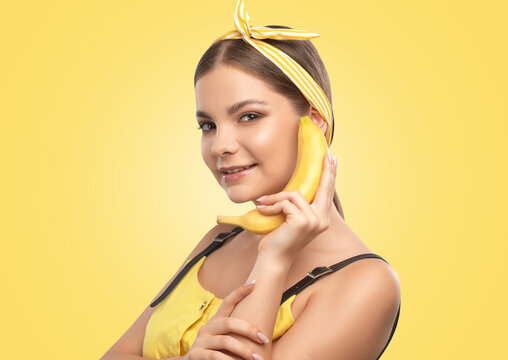 Portrait of a beautiful brunette girl with healthy clean skin and fresh make-up on a yellow background. She holds a banana. Healthy nutrition concept.