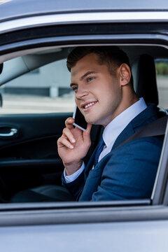Smiling businessman in formal wear talking on smartphone in auto.