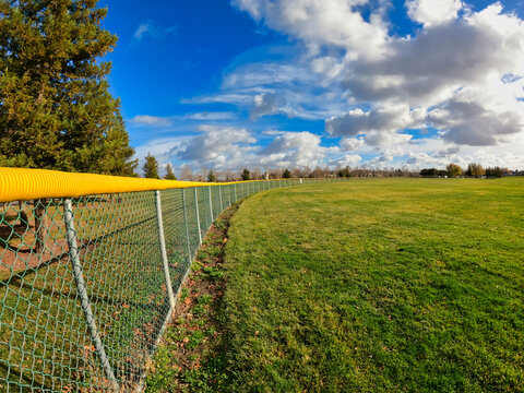 Outfield fence at a baseball field on a cloudy day
