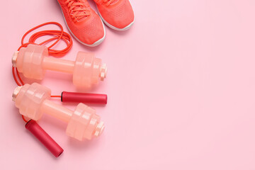 Dumbbells, sport shoes and skipping rope on color background
