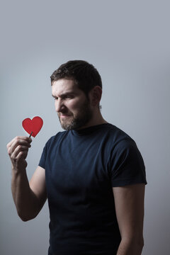 man in black shit holding a paper heart with tweezers and looking at it with disgust showing negative emotions