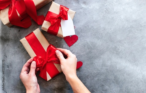 hands holding a present gift boxes with red ribbon. Valentine's day, birthday present, mother's day concept