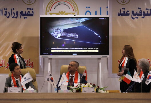An image is displayed on a screen as Iraq's director general at the General Company for Ports, Farhan al-Fartousi, signs a contract with South Korea's Daewoo Engineering & Construction, to construct the Grand Faw port, in Baghdad