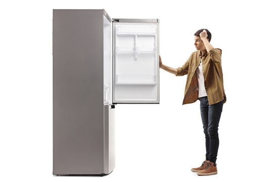 Young man in panic looking at an empty fridge