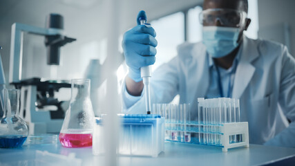 Medical Development Laboratory: Black Scientist wearing Face Mask Uses Micro Pipette, Filling Test...