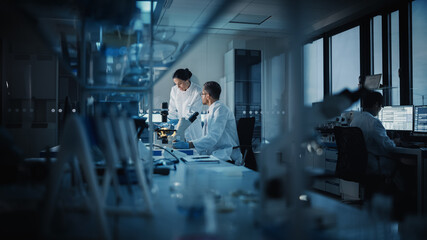 Modern Medical Research Laboratory: Two Scientists Working, Using Digital Tablet, Analyzing Test,...