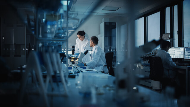 Modern Medical Research Laboratory: Two Scientists Working, Using Digital Tablet, Analyzing Test, Talking. Advanced Scientific Pharmaceutical Lab for Medicine, Biotechnology Development. Evening Time