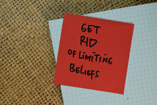 Get Rid Of limiting Beliefs write on sticky notes isolated on Brown burlap laying on table