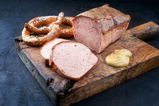 Traditioneller ofenfrischer bayrischer Leberkäse aufgeschnitten und am Stück serviert mit frischer Breze und scharfen Senf als close-up auf einem alten rustikalen Holz Board