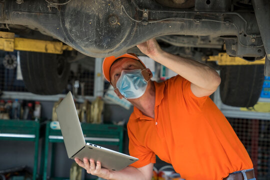 Senior car mechanic supervisor wearing mask and holding laptop to inspect the engine, repair car in the garage.