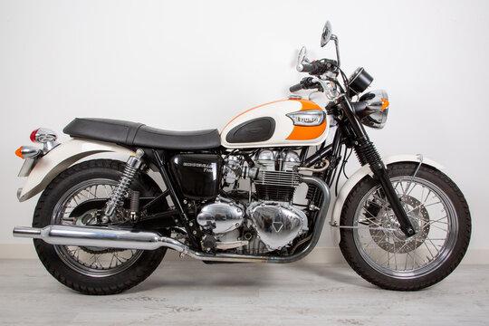 triumph bonneville t100 bonnie carburetor white orange bike detail side studio view