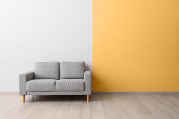 Stylish cozy sofa near color wall