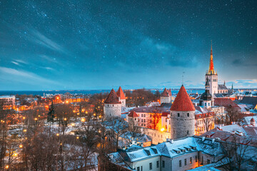 Fototapeta Tallinn, Estonia. Night Starry Sky Above Old Castle Walls Architecture. Cityscape Skyline In Old Town. Winter Evening Night. Famous Landmark. Popular Destination Scenic. UNESCO Heritage. Altered Sky.