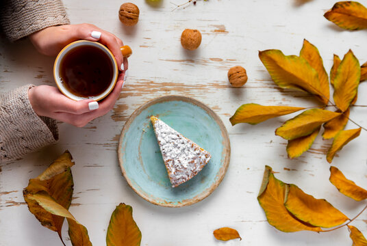 Woman's hands holding hot cup of tea on the table with autumn leaves and pie. Top view