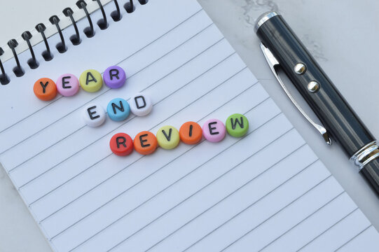 Selective focus of notebook, pen and colorful alphabet beads written with text YEAR END REVIEW.