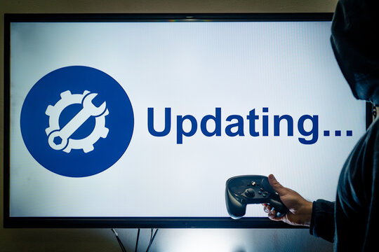 Hooded man holding a gaming controller in front of a screen showing an updating message for a game or software day 1 patch