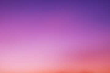 Early morning light sky before sunrise. Soft purple, pink and orange light on the horizon. Empty natural sky with colorful pastel tone colors for background. Vivid colors in modern mood.