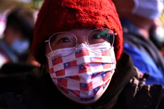 A woman wears a face mask with a Taiwan flag print during a New Year celebration in Taipei