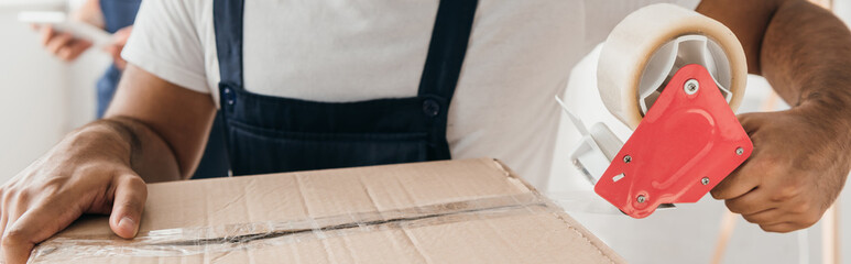 Fototapeta partial view of man holding scotch tape while packing box