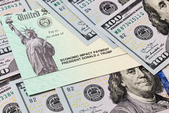 United States Treasury check and 100 dollar bills. Concept of stimulus payment, small business, federal government, grant, loan, benefit and assistance