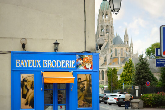 A general view of the Bayeux Broderie Shop sign with the historic Cathedral in view, in the historic town of Bayeux France on September 21 2019>