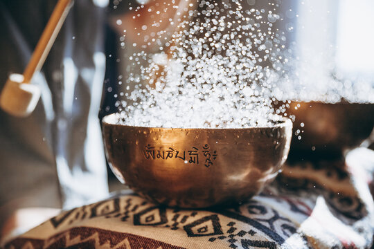 Nepal Buddha copper singing bowl at spa salon. Young bearded man doing massage therapy singing bowls in the Spa. Sound therapy, recreation, meditation, healthy concept