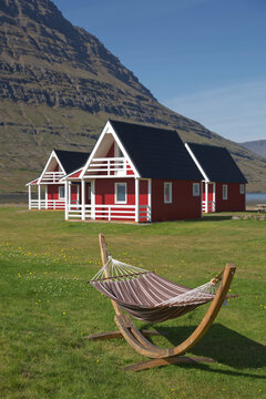 Traditional red painted wooden panel house with mighty Holmatindur mountain in the background in Eskifjordur, East Iceland