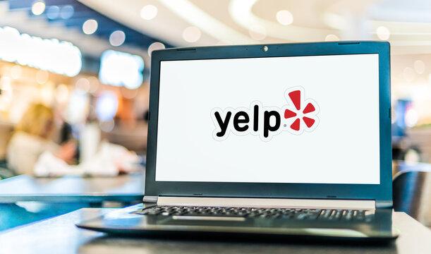 Laptop computer displaying logo of Yelp