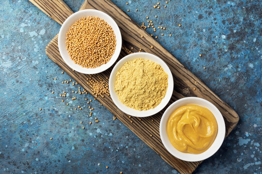 Set of yellow mustard sauce, powder and seeds in small bowls