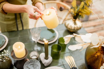 Young female lighting candles while decorating dinning table in natural Boho style in green tones outdoors