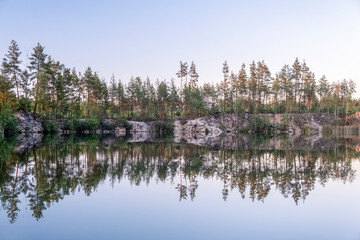 Panoramic view of a beautiful clear lake among granite rocks and a pine forest reflected in the...