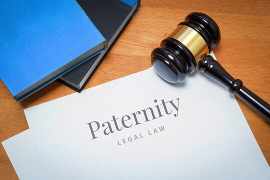 Paternity. Document with label. Desk with books and judges gavel in a lawyer's office.