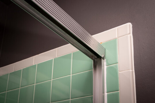 View of sliding shower door frame, in retro colored and styled home bathroom setting.