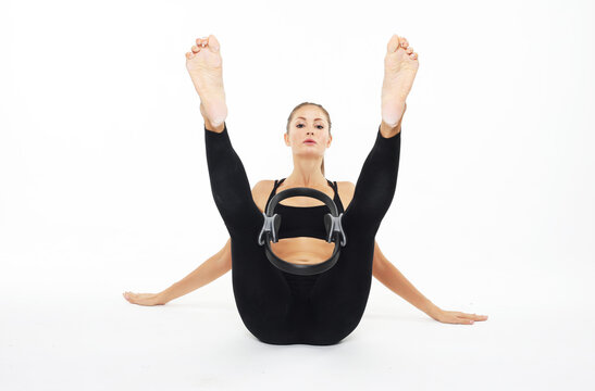Young sporty woman with perfect body sitting on the floor and having a training with pilates ring