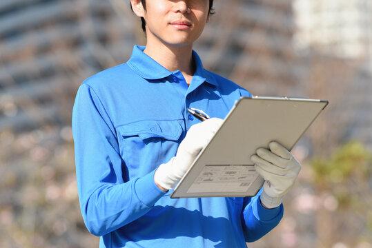 メモを取る作業服姿の男性