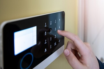 Obraz Man's hand pressing the alarm system button. Home security. - fototapety do salonu