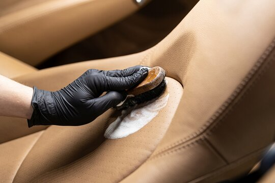 Cleaning leather car seat and upholstery with brush. Car detailing