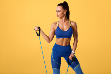 Fitness woman working out with resistance band on orange background. Athletic girl exercises with expander