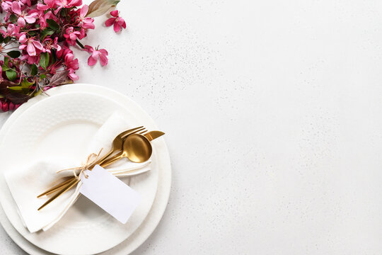 Spring elegance table setting with apple tree flowers, golden cutlery and tag on white table. View from above. Space for text.